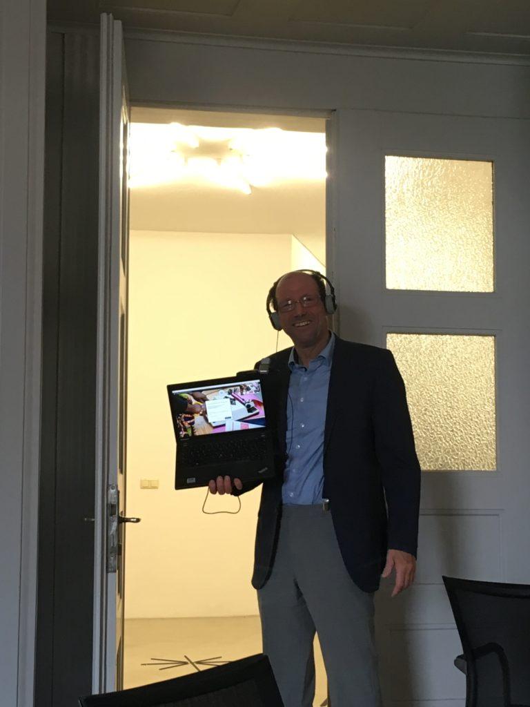 Philipp Schramm unterwegs mit Laptop, Mikrofon und Kamera live bei seiner Online-Führung durchs Iwalewahaus