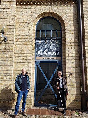 Nach gemeinsamer Geländeerkundung haben sich Karl Elbl und Jürgen Trinkus vor der Reithalle unter das Ankündigungsschild der Ausstellung gestellt